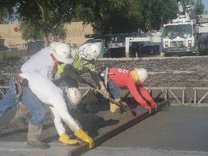 Construction workers in hard hats drag level over freshly poured concrete
