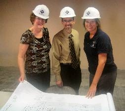 Three charter school board members with construction plans and hard hats
