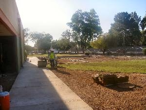 Workers roll out sod on charter school playground
