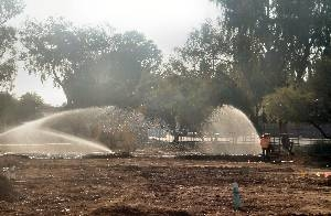 Sprinklers prepare dirt playground of traditional charter school for sod