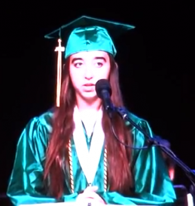 Teenage girl in green graduation cap and gown speaking at graduation ceremony