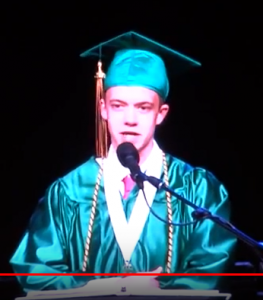 Teenage boy in green graduation cap and gown speaking at graduation ceremony