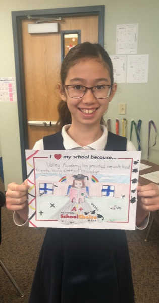"""Smiling girl with glasses holds sign """"Valley Academy has provided me with kind friends, loving staff, and knowledge!"""