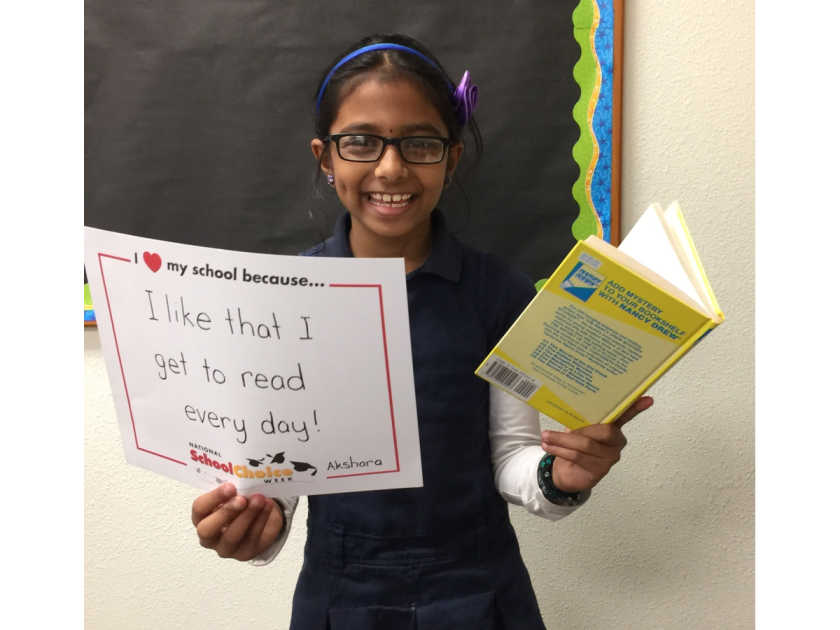 """smiling middle school girl holds book and sign saying """"I like that I get to read every day."""""""