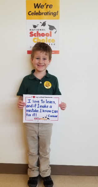 """Smilling kindergarten boy holds sign """"I love to learn, and if I make a mistake, I know I can fix it --Connor"""""""
