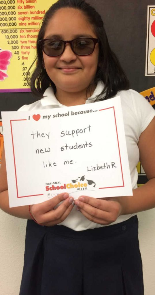 """MIddle school girl with dark glasses holds sign """"I love my school becuase they support new students like me. __Lizbeth R."""""""